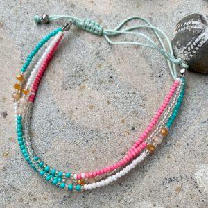 Tre armbaand med perler i ét paa sten