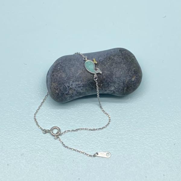 Caroline armbaand i soelv med lyseblaat hval-vedhaeng lagt paa sten