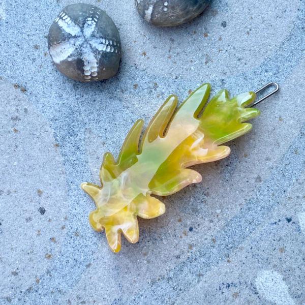Gult haarspaende formet som et blad paa sten