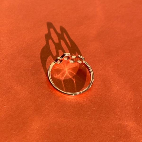 Joleen soelvring belagt med rosegold og formet med sekskanter paa orange baggrund