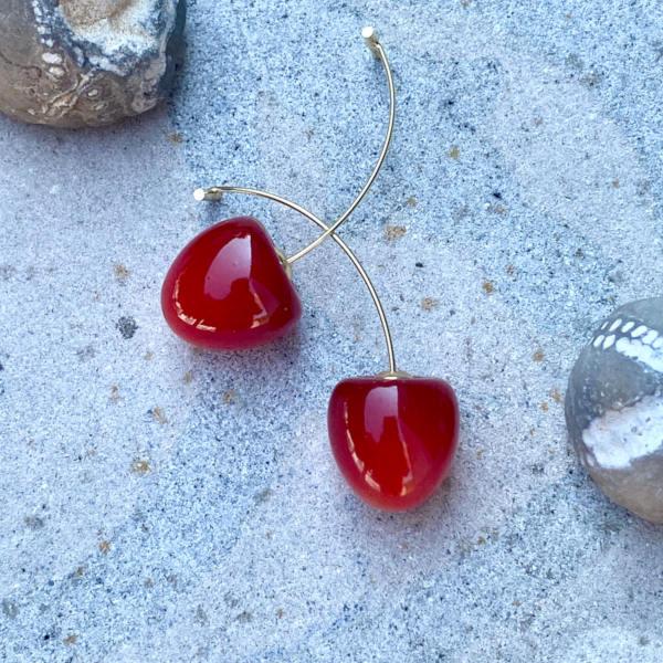 Oereringe med lille kirsebaer i dyb roed med gylden stilk paa sten