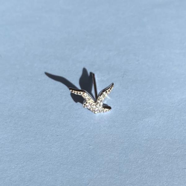 Sienna oerestik i soelv med zirkoner, formet som fugl, der spreder sine vinger paa lyseblaa baggrund