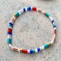 Armbaand med flade perler i mange farver paa sten