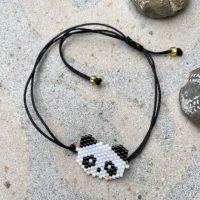 Armbånd i sort snor med panda ansigt i perler paa sten