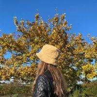 Bea boellehat i gult lammelook paa model i efteraars skov