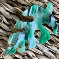 Groent haarspaende formet som et blad paa fletbaggrund