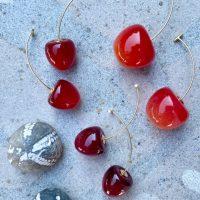 Oereringe med kirsebaer med gylden stilk paa sten