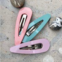 Haarspaender i oversize i lyseroed, lilla og mint paa sten