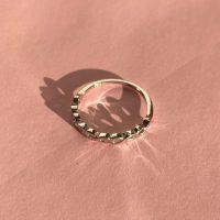Liva soelvring med snoning i evighedsmoenster paa rosa baggrund