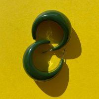 Maude moerkegroenne oereringe formet som halvmaaner paa gul baggrund