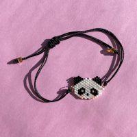 Mindy armbaand af sort traad med panda ansigt lavet i perler paa rosa baggrund